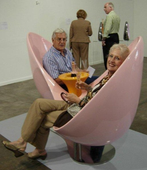 David and Marsja Hall Green relax in Karim Rashid's Love Seat at the Yellow by Design exhibition at Arts on Main, Johannesburg